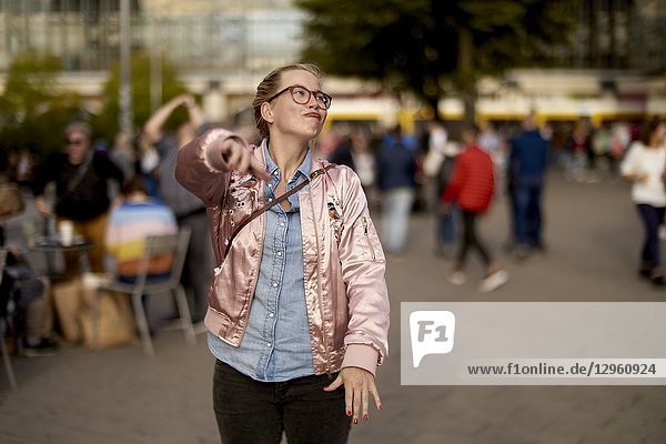 Lively woman with open arms dancing at Alexanderplatz  Berlin  Germany