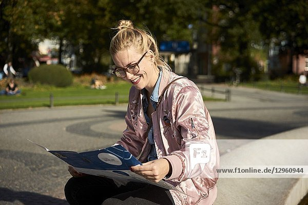Woman reading city guide map  in Berlin  Germany