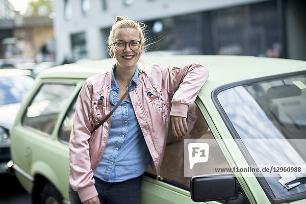 Portrait of woman leaning against vintage car in Berlin  Germany