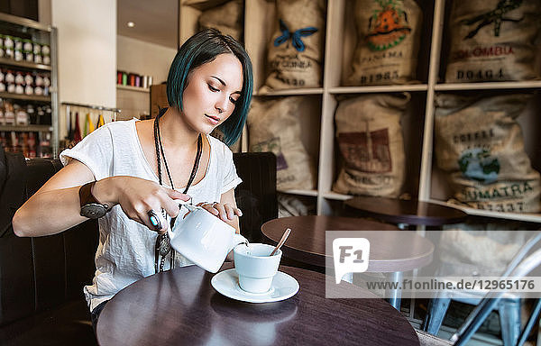 Young woman in front of her cup of tea in a bar
