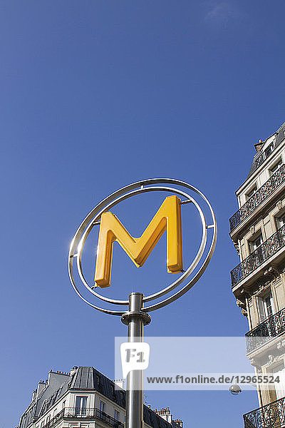 'France  Paris  department 75  metro signage: yellow ''M'' letter with a blue sky in the background.'