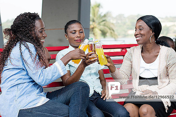 young women celebrating their reunion with beautiful smiles and drink in their hands.