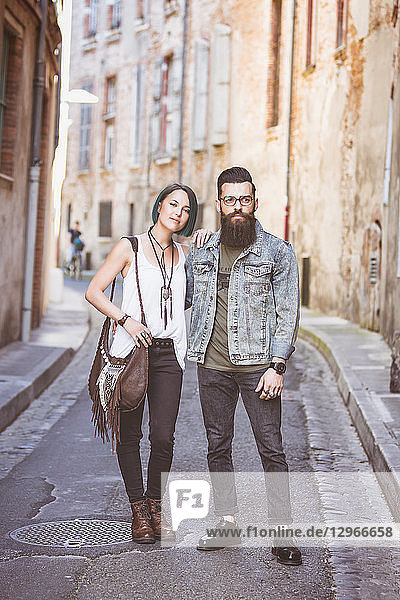 Young hipster couple walking arm in arm  on street