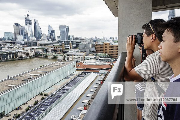 United Kingdom Great Britain England  London  Bankside  River Thames  Tate Modern art museum terrace view  city skyline  downtown skyscrapers  rooftops  gray sky  Asian  man  boy  teen  looking  taking photo