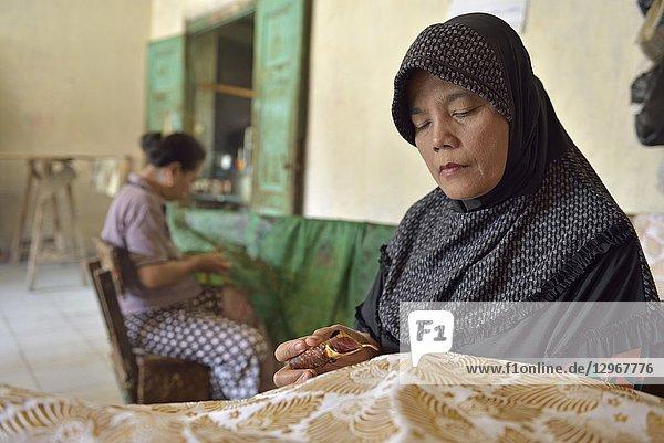 Women using a pen-like tool  called ''canting''  to apply liquid hot wax in the batik-making process  Wirakuto batik workshop  Pekalongan  Java island  Indonesia  Southeast Asia.