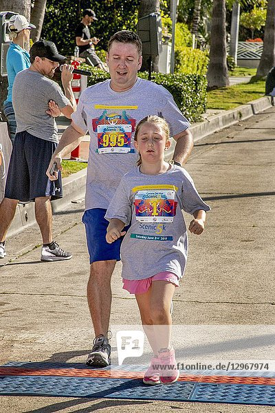 A father encourages his exhausted 8-year-old daughter across the finish line of a a weekend 5K foot race in Newport Beach  CA.