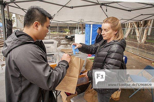 To combat opiate overdoses  multiracial volunteers distribute Naloxone antidote kits in paper bags at a homeless encampment in Santa Ana  CA.