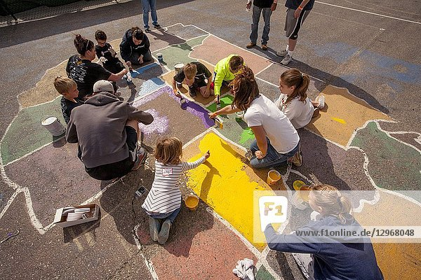 A faded playground map of the USA in a Costa Mesa  CA  elementary school playground gets a new coat of paint from multiracial volunteers of all ages.