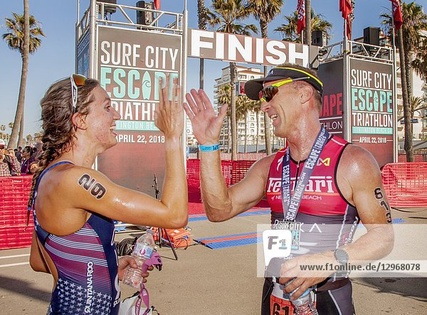 Sweating athletes of both sexes congratulate each other at the finish line of a triathlon competition in Huntington Beach  CA. Note numbers on bare arms.