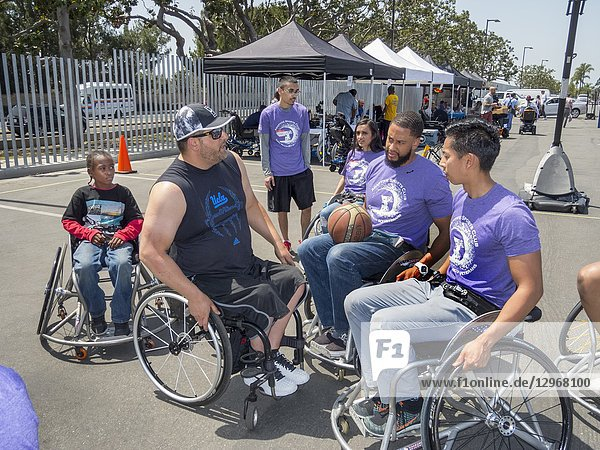 Multiracial handicapped members of a wheelchair basketball team prepare for a game at an Adaptive Sports Expo in a Long Beach  CA  parking lot.