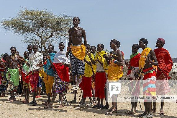 A group of young Samburu men dressed in traditional clothing performing a traditional jumping dance at a Samburu village near Samburu National Reserve in Kenya.