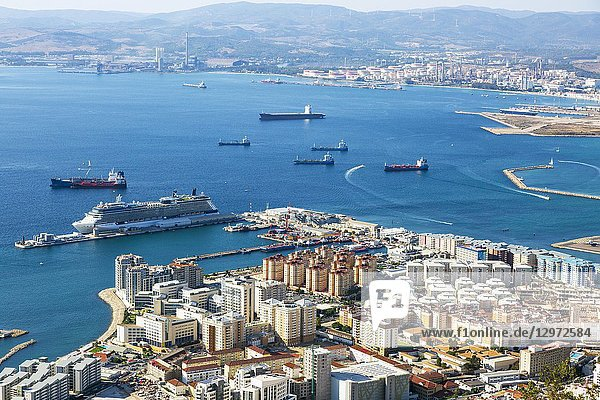 High view over Gibraltaharbour with a cruise liner berthed at Western Arm of Container Quay  and a view over the Bay of Gibraltar to the Spanish mainland.