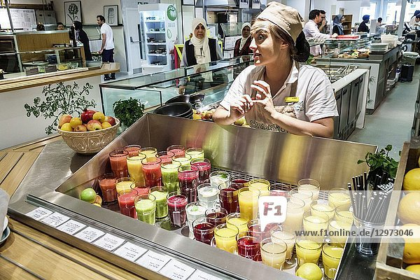 United Kingdom Great Britain England  London  Marylebone  Selfridges Department Store  shopping  inside interior  upmarket  luxury retail  The Selfridges Kitchen  cafeteria  restaurant  counter  fruit juices  woman  attendant  employee