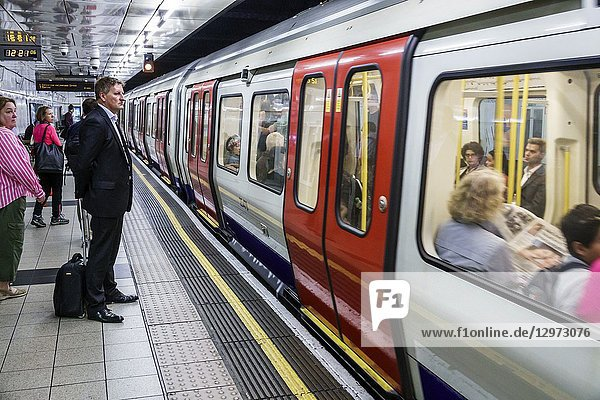 United Kingdom Great Britain England  London  Lambeth South Bank  Waterloo Underground Station  subway tube  public transportation  platform  man  passenger  commuter  train  arriving departing