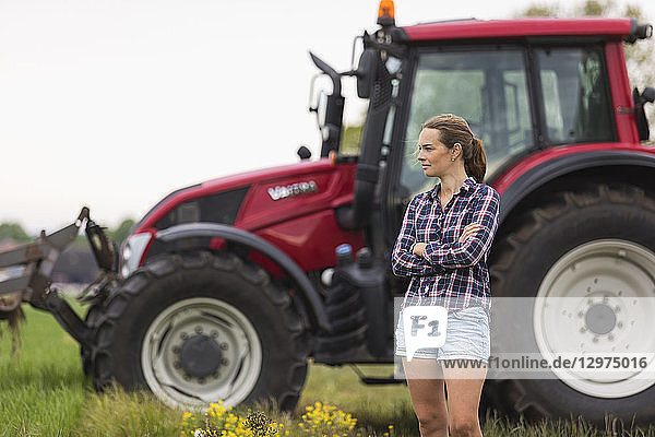 Agricultural worker standing in front of tractor
