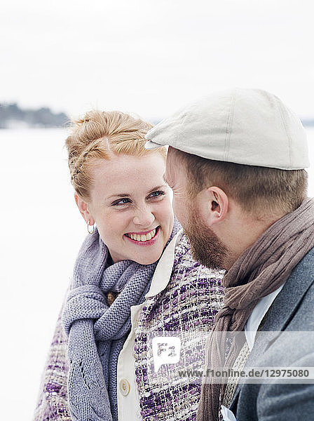 Young man and woman smiling in the snow in Sweden