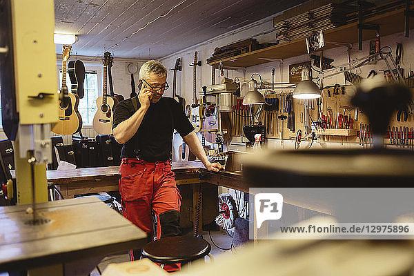 Craftsman on phone in guitar making workshop