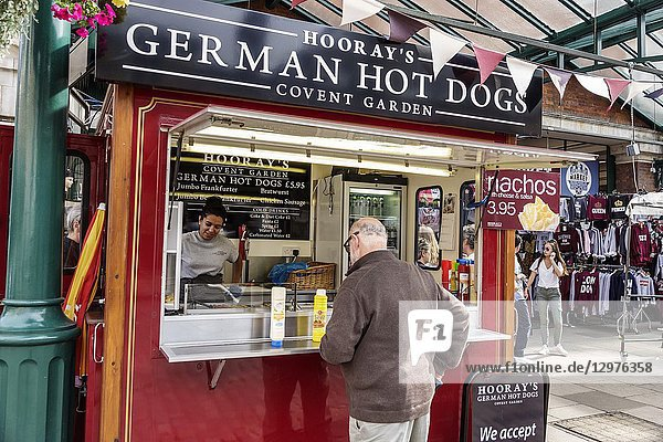 United Kingdom Great Britain England  London  Covent Garden  market  shopping dining entertainment  German hot dogs kiosk  Hooray's  man  woman