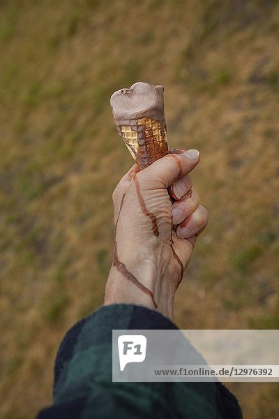 Man's hand holding a dripping chocolate ice cream cone against the ground.