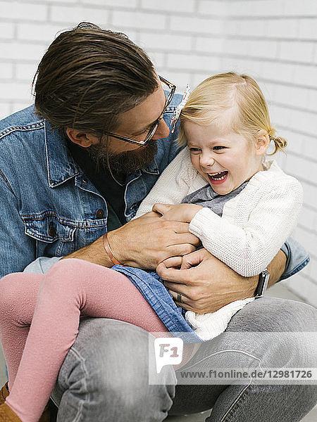 Man tickling his daughter