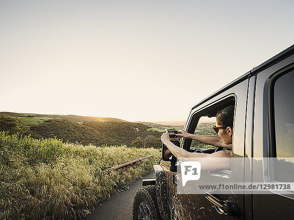 Woman in off road vehicle photographing sunset