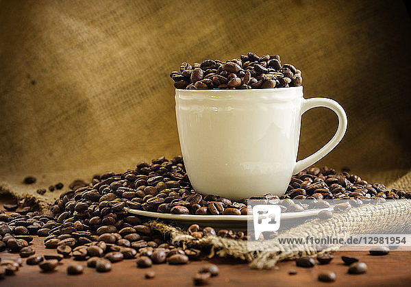 Coffee beans in cup and saucer