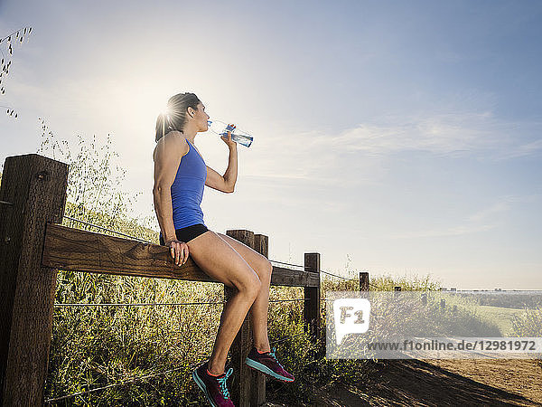 Woman in sportswear drinking from water bottle