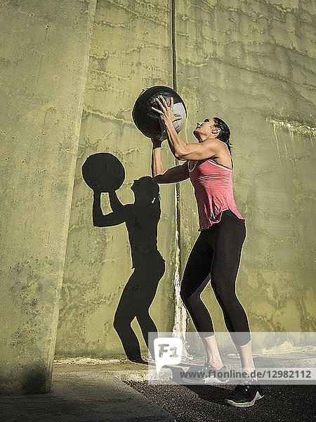 Woman throwing medicine ball against concrete wall