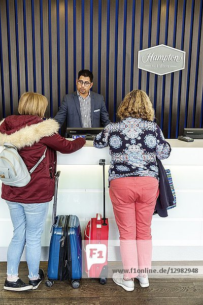 United Kingdom Great Britain England  London  Lambeth South Bank  Hampton Hilton Waterloo  hotel  inside interior  front desk  check-in  clerk  guest  Asian  man  woman  service  luggage rolling suitcase
