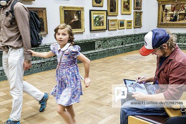 United Kingdom Great Britain England  London  Westminster  Millbank  Tate Britain art museum  inside interior  gallery  paintings  man  copyist  drawing  sketching  ipad tablet  stylus  girl  walking