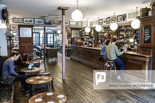 England  London  South Bank Southwark  Union Street  Mc & Sons Pub  traditional old Irish boozer  public house bar  worn out wood bench tables  hardwood floors  man  woman  empty  drinking  inside