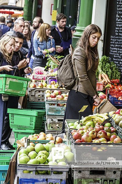 England  London  South Bank Southwark  Borough Market  vendors stalls  produce  fruits vegetables  apple crates  woman  man  shopping  baskets  selecting