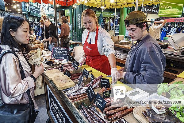 England  London  South Bank Southwark  Borough Market  vendors stalls  Cannon & Cannon  cured meat  charcuterie  Asian  woman  man  sellling  display sale