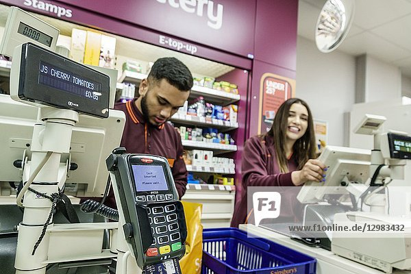 United Kingdom Great Britain England  London  Lambeth South Bank  Sainsbury's grocery supermarket convenience store  inside interior  cashiers  check-out  Black  man  woman  young adult  working  credit card pin pad