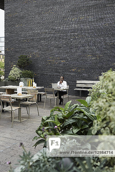 Pensive businesswoman sitting with laptop on roof terrace of a coffee shop