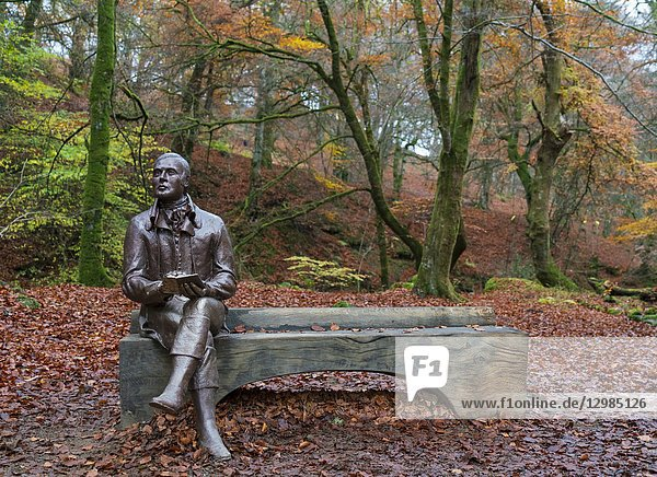 Statue of poet Robert Burns sits on bench during autumn at the Birks O'Aberfeldy scenic area in Aberfeldy  Perthshire  Scotland UK.
