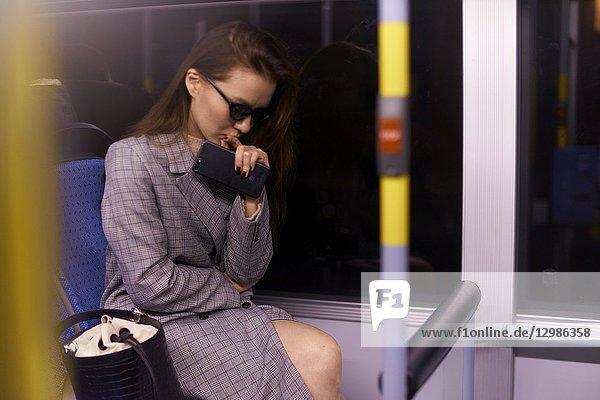 Woman in tram by night. Munich  Germany.
