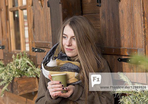 Frau steht vor Holzhütte  mit heißem Getränk