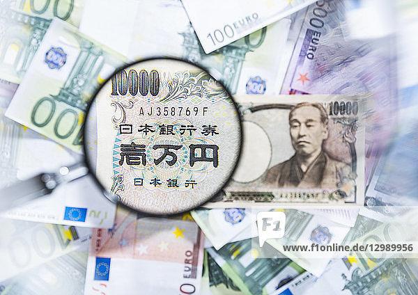 Japanische Yen mit Lupe und EURO-Banknoten