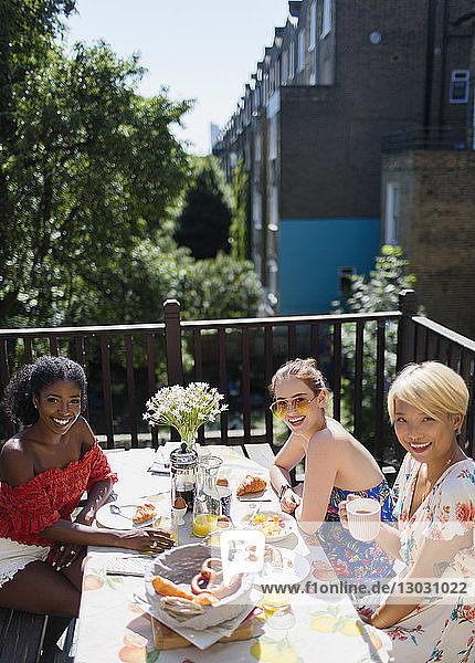 Portrait smiling young women friends enjoying brunch on sunny apartment balcony