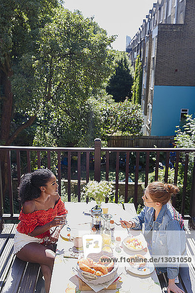 Young women friends enjoying brunch on sunny urban apartment balcony