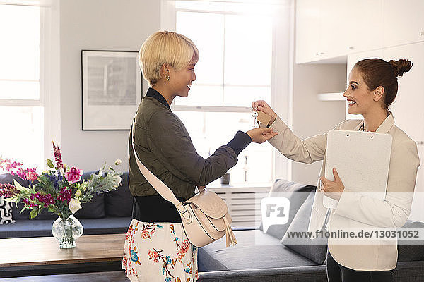 Real estate agent giving apartment keys to young woman