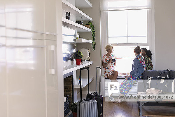 Young women friends talking in house rental window