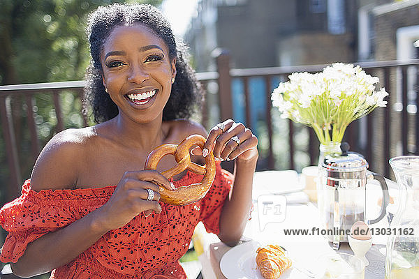 Portrait smiling  confident young woman with pretzel enjoying breakfast on sunny balcony