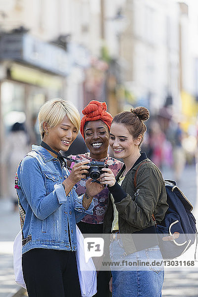 Young women friends using digital camera on urban street