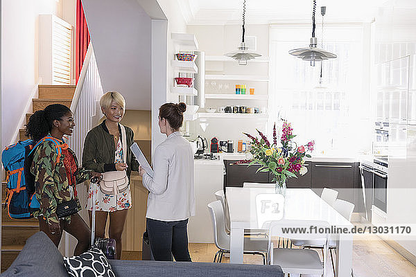 Real estate agent greeting young women friends arriving at house rental