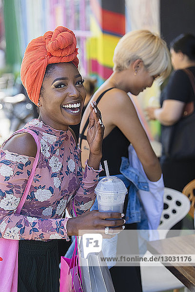 Portrait happy  carefree young woman in headscarf drinking smoothie
