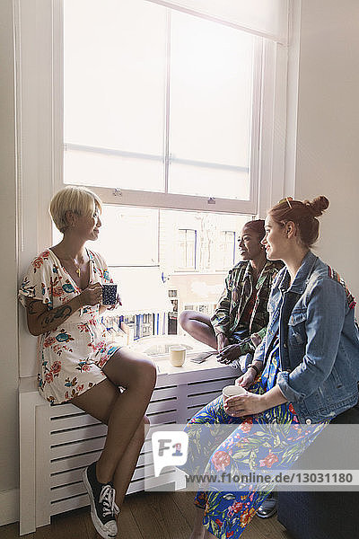 Young women friends talking and drinking tea in apartment window