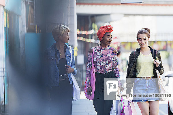 Young women friends walking with shopping bags on urban sidewalk