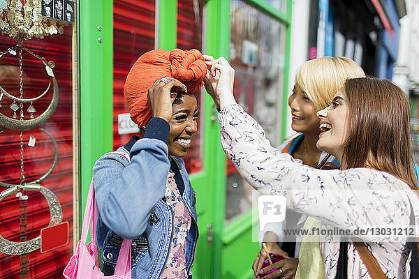Young women helping friend adjusting headscarf on urban sidewalk